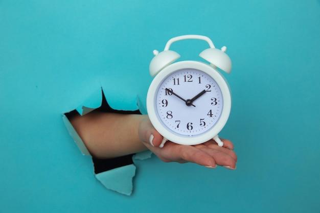 Mão de mulher segura o despertador através de um buraco de papel. conceito de gerenciamento de tempo e prazo.