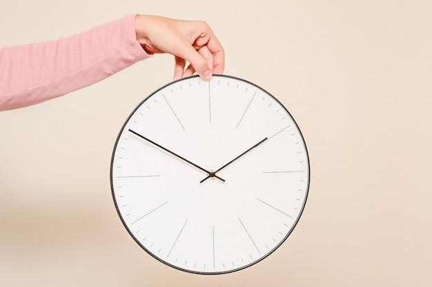 Mão de mulher segura o relógio de parede em um fundo branco