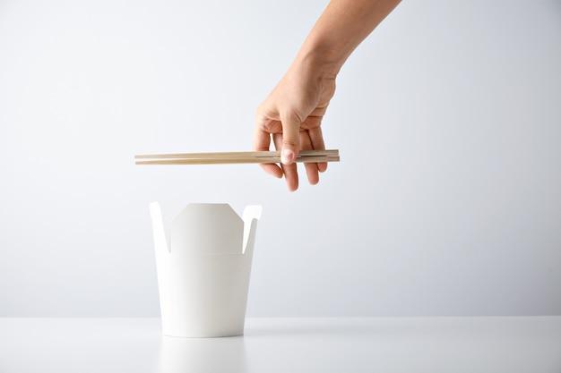 Mão de mulher segura pauzinhos acima da caixa de entrega em branco aberta com macarrão saboroso isolado no branco. apresentação do conjunto de varejo