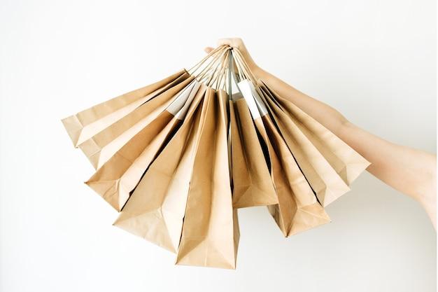 Mão de mulher segura sacos de papel artesanal na superfície branca.