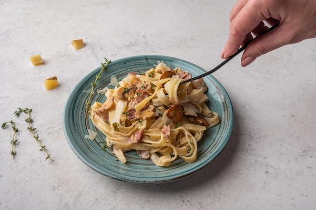 Mão de mulher segura um garfo com macarrão fettuccine com cogumelos, bacon e queijo parmesão no prato