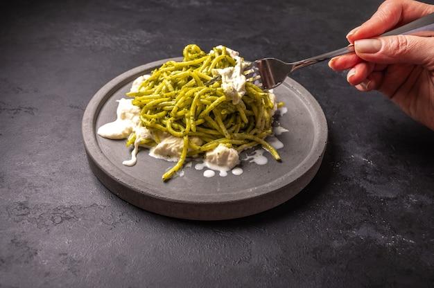 Mão de mulher segura um garfo com uma pasta com strachatella e pesto, foco seletivo, close-up