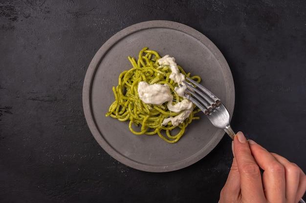 Mão de mulher segura um garfo com uma pasta com strachatella e pesto, foco seletivo, vista de cima
