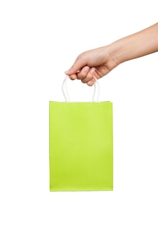 Mão de mulher segura uma bolsa verde brilhante para compras isolado na parede branca