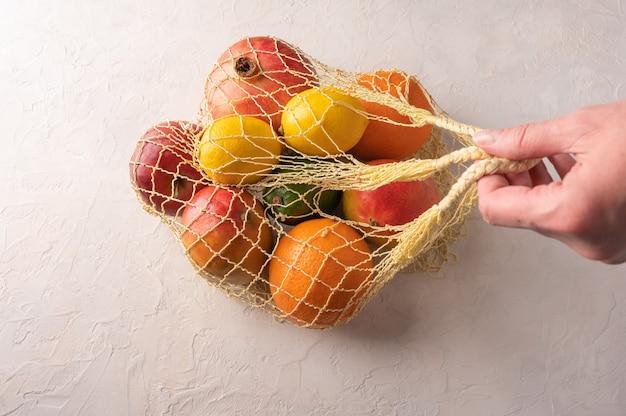Mão de mulher segura uma mistura de frutas orgânicas, vegetais e verdes em um saco de barbante sobre fundo claro.