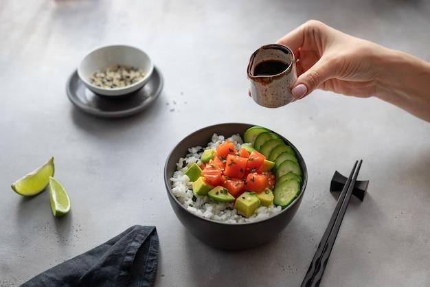 Mão de mulher segura uma panela com molho de soja sobre uma tigela escura com salmão, arroz, abacate e pepino. salada tradicional havaiana de peixe cru.