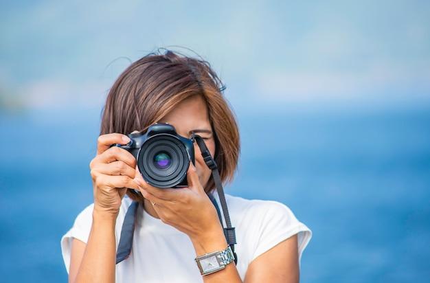 Mão de mulher segurando a câmera tirar fotos de fundo