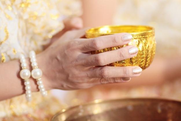 Mão de mulher segurando a taça de ouro