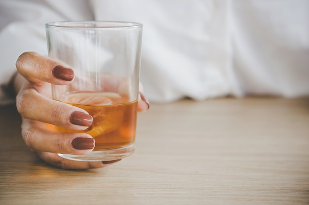 Mão de mulher segurando álcool vidro bebendo