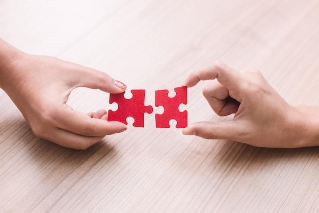 Mão de mulher segurando as peças do quebra-cabeça no escritório
