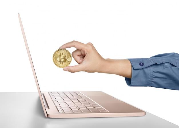 Mão de mulher segurando bitcoin dourado na frente de um laptop