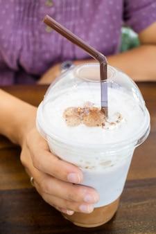 Mão de mulher segurando café gelado