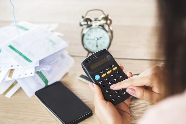 Mão de mulher segurando calculadora contando dívida