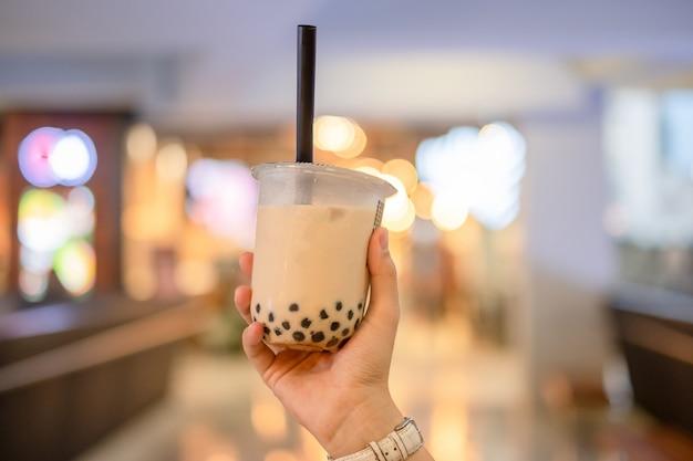 Mão de mulher segurando chá de bolha de leite gelado