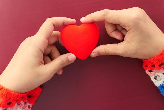 Mão de mulher segurando coração vermelho de perto
