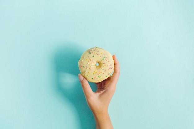 Mão de mulher segurando donut sobre fundo azul