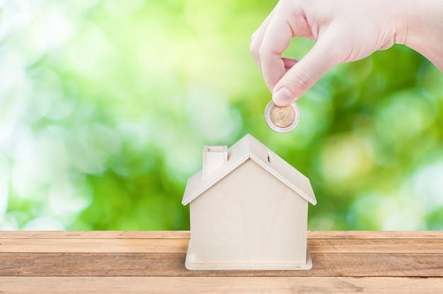 Mão de mulher segurando moedas banco da casa economizar dinheiro, fundo verde da natureza conceito de investimento e economia