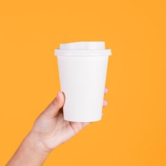 Mão de mulher segurando o copo descartável branco sobre fundo amarelo