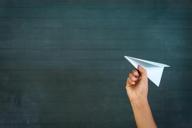 Mão de mulher segurando o foguete de papel branco com fundo de lousa