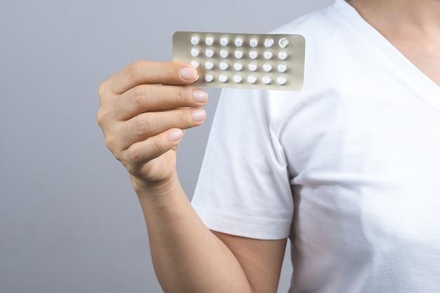 Mão de mulher segurando o pacote de pílulas anticoncepcionais, medicina de controle de natalidade