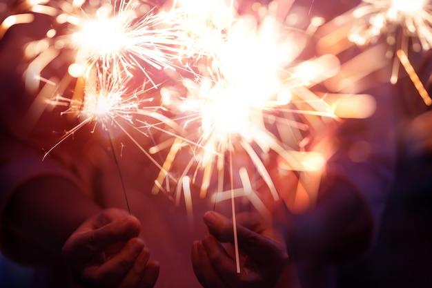Mão de mulher segurando pirotecnia de fogo de artifício e bokeh com efeito embaçado