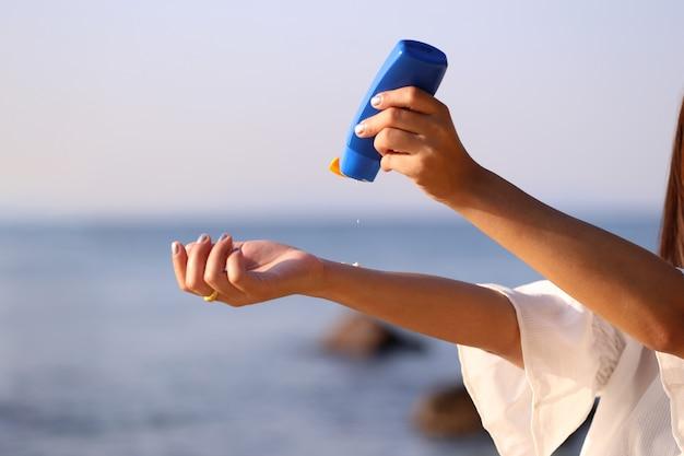 Mão de mulher segurando protetor solar na praia com o mar no fundo do céu azul, proteção de protetor solar spf e conceito de cuidados com a pele