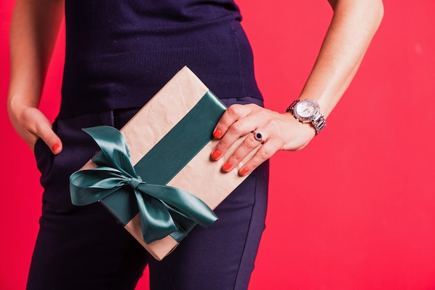 Mão de mulher segurando um presente no fundo rosa do estúdio