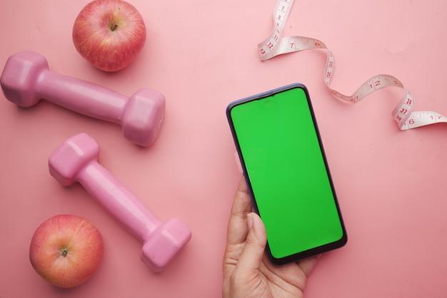 Mão de mulher segurando um telefone inteligente com halteres e maçã rosa