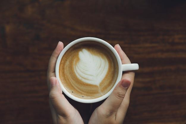Mão de mulher segurando uma caneca de café branco