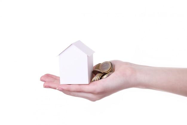 Mão de mulher segurando uma pequena casa isolada no branco