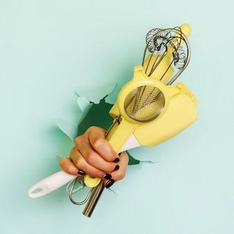 Mão de mulher segurando utensílios de cozinha em fundo azul