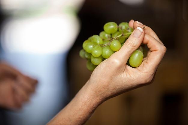 Mão de mulher segurando uvas