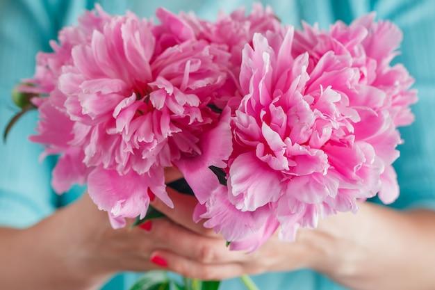 Mão de mulher segurar flor de peônia branca.