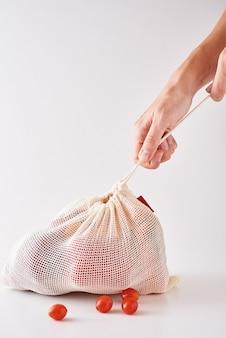 Mão de mulher segurar legumes orgânicos frescos na sacola de têxteis.