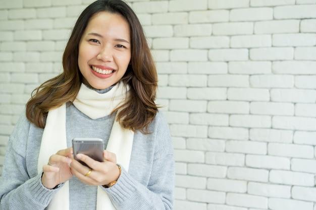 Mão de mulher segurar o telefone móvel para o trabalho ou o jogo