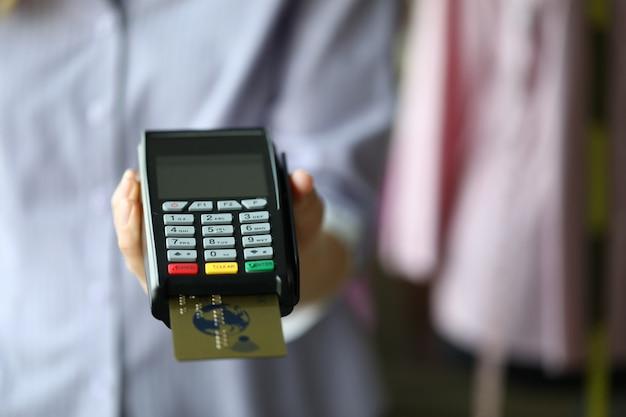 Mão de mulher segurar pos termimal com cartão de débito plástico ouro