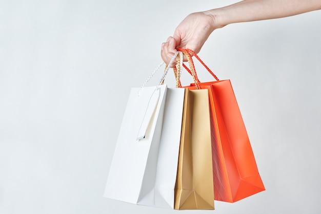 Mão de mulher segurar sacolas de papel colorido em um branco, close-up