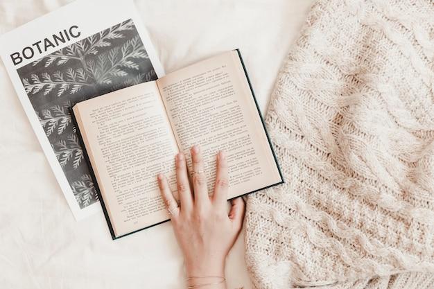 Mão de mulher sendo no livro deitado no banner e cobertor no lençol