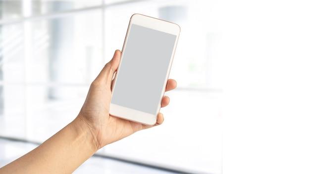 Mão de mulher senhora segurando o telefone móvel com espaço de cópia.
