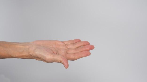 Mão de mulher sênior ou mais velha fazendo convite sobre fundo branco.