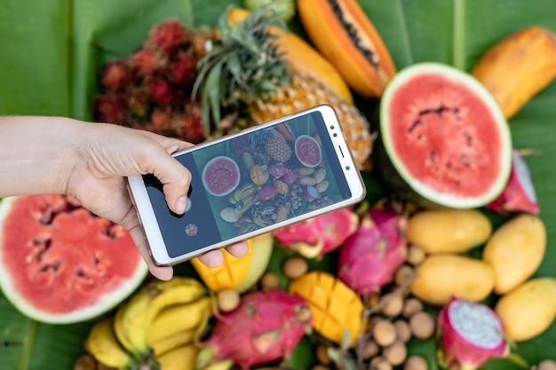 Mão de mulher tirando fotos de frutas tropicais no celular