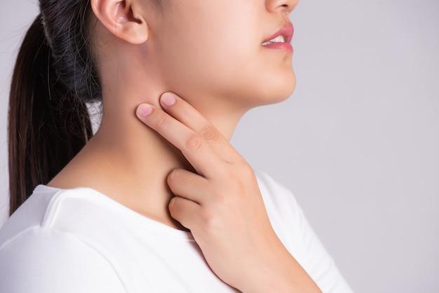 Mão de mulher tocando seu pescoço doente