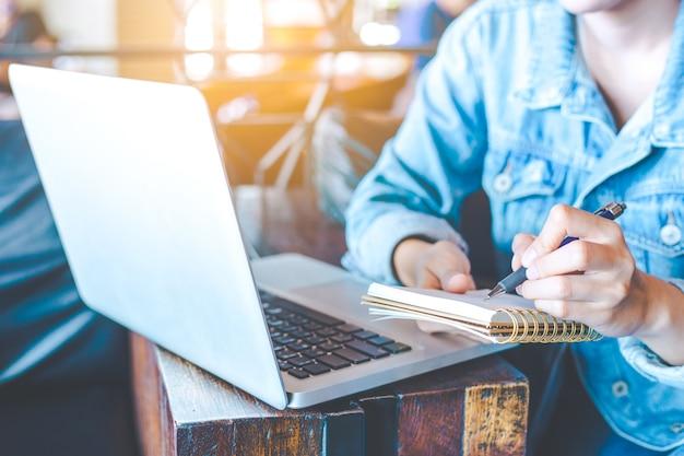 Mão de mulher trabalha em um computador portátil e está escrevendo em um bloco de notas com uma caneta em um escritório