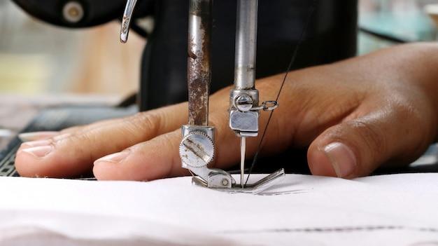 Mão de mulher, trabalhando com a máquina de costura