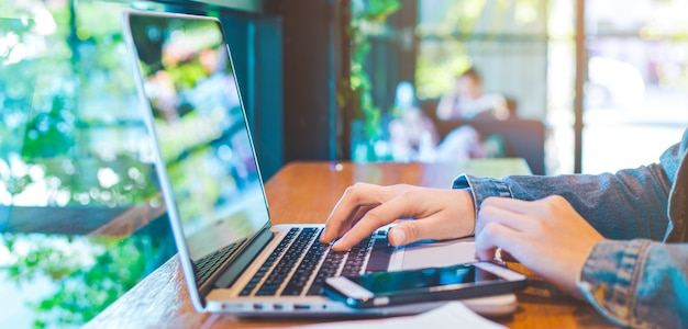 Mão de mulher trabalhando no laptop no escritório.