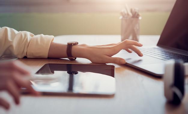 Mão de mulher trabalhando no tablet e pressione o laptop em cima da mesa no escritório.