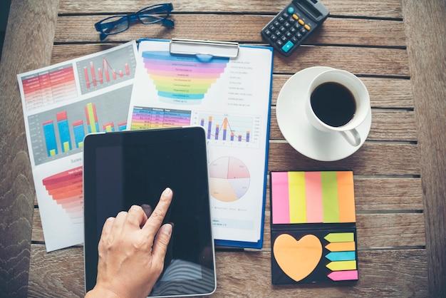 Mão de mulher usa tablet inteligente office laptop negócios gráfico gráfico financeiro na mesa com a xícara de café