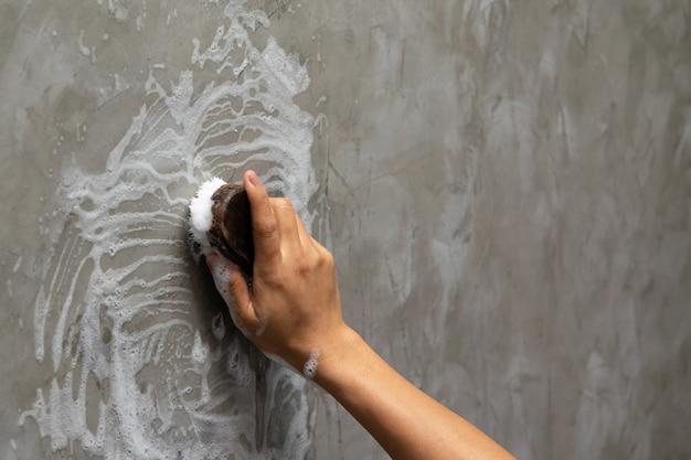 Mão de mulher usada para converter a limpeza de polimento na parede de concreto