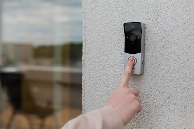 Mão de mulher usando campainha na parede da casa com câmera de vigilância