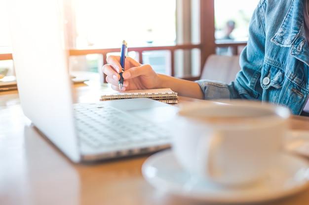 Mão de mulher usando laptop e escrevendo no bloco de notas